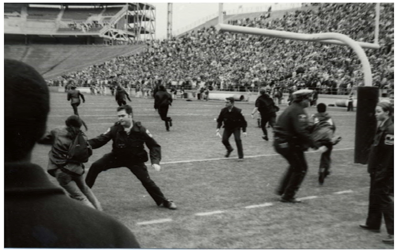 Students rush on the field of Beaver Stadium to protest and are met by police