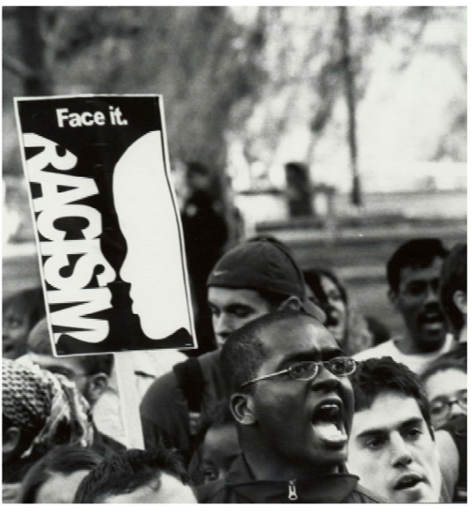 "A young male protester holds a sign that reads ""racism - face it."""